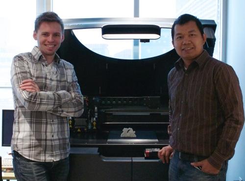 James Wetzel and Bounnak Thommavong in front of Mark Ginsberg's 3D printer.